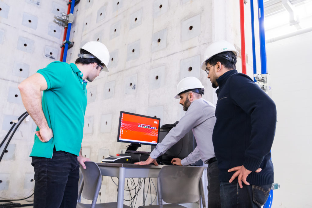 Image of three engineerings students standing around a computer