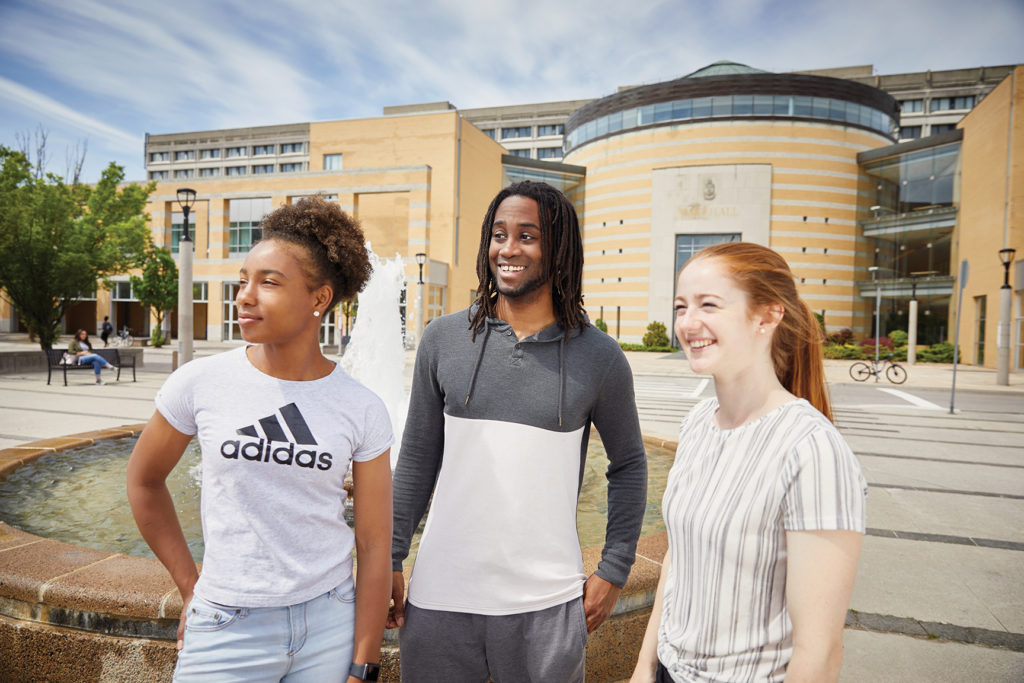 Image of three students smiling and standing in front of Vari Hall