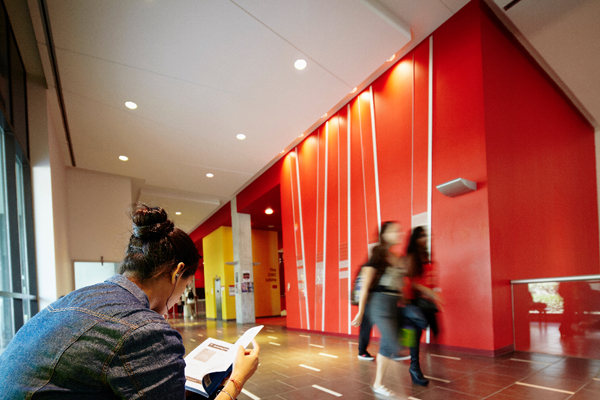images of students walking in a hallway while another student is sitting down, reading