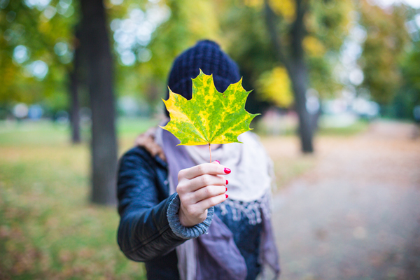 photo of a female holding a maple leaf in front of her face