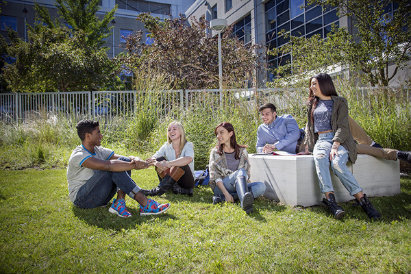 photo of a group of students sitting in a courtyard talking