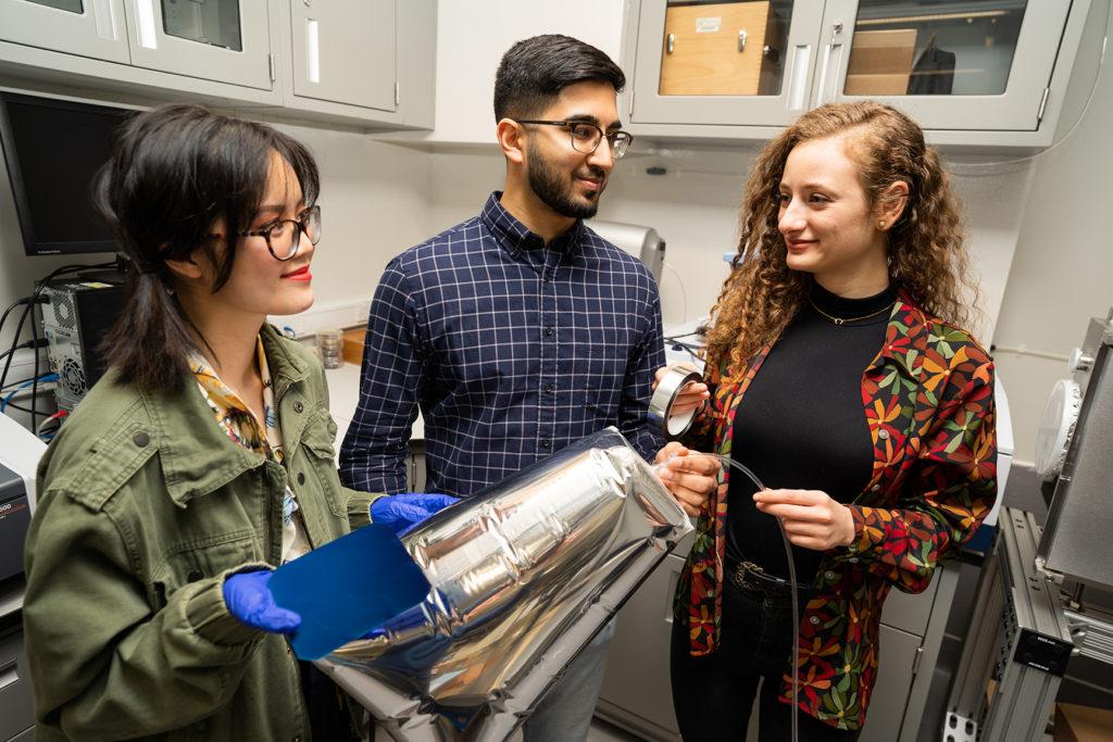 Three students talking in a lab