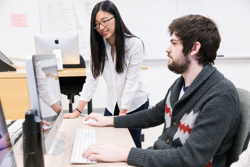 Two students talking in front of a computer