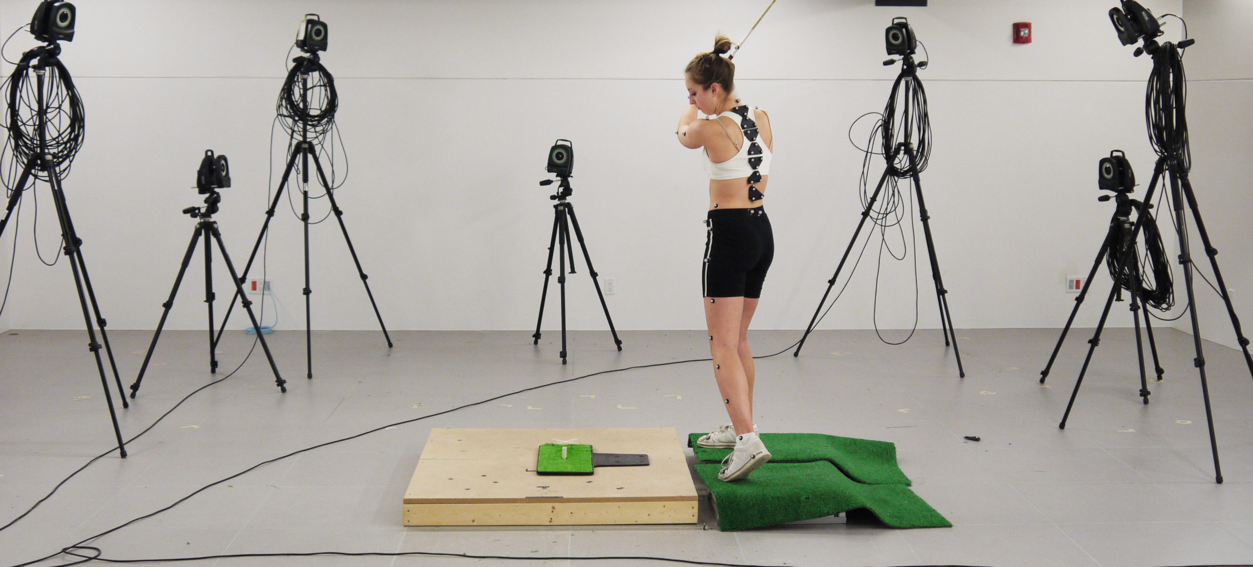 Kinesiology student swinging a golf club in a motion study