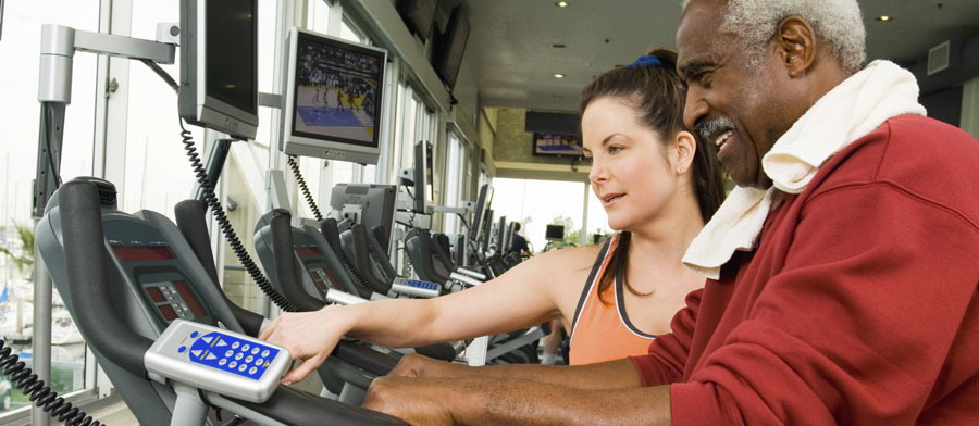 Trainer with a senior client on a treadmill