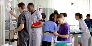 Nursing students standing next to a simulation dummy in a hospital