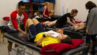 Kinesiology students practicing physical therapy