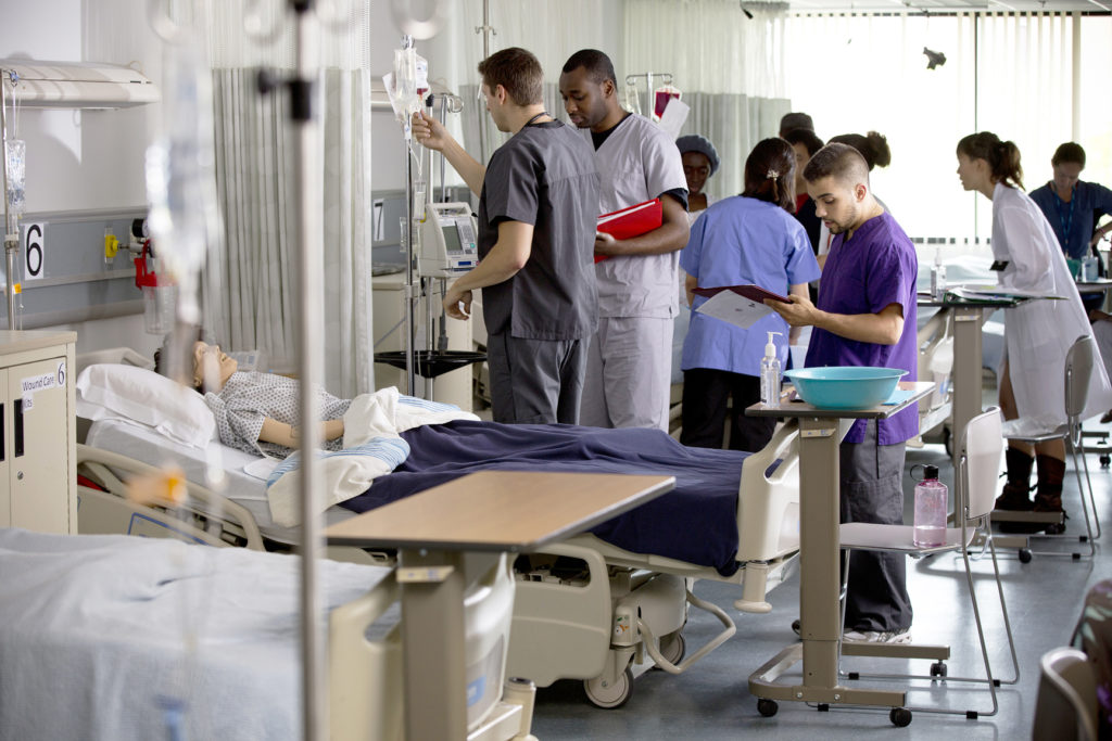 Nursing students standing by a simulation dummy in a hospital