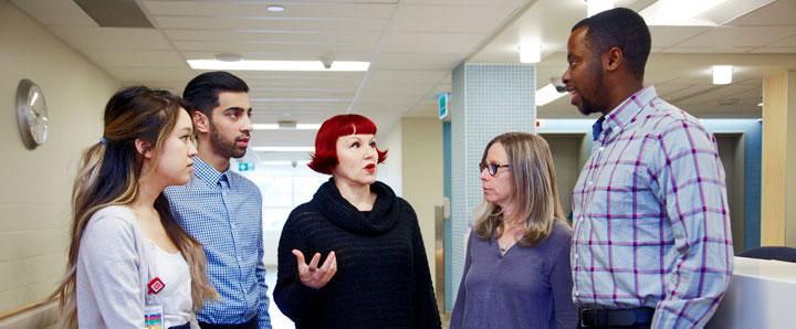 Health studies professor speaking to students in a hospital