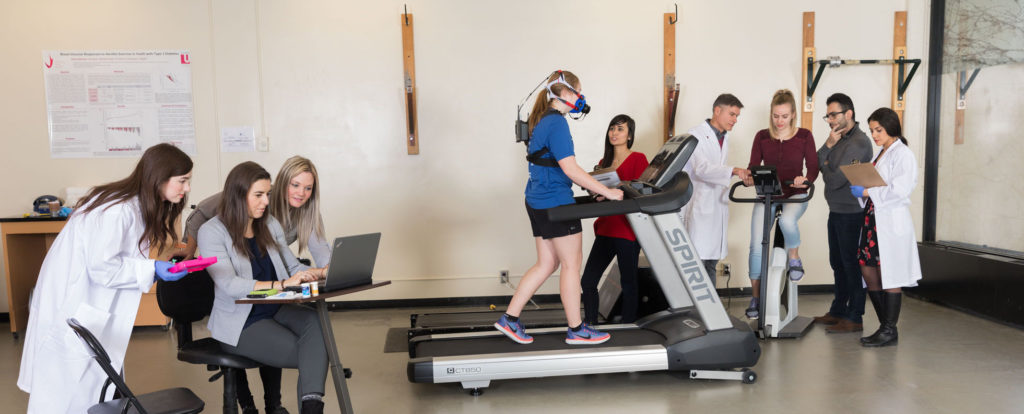 Researchers in a lab studying a Kinesiology student on a treadmill