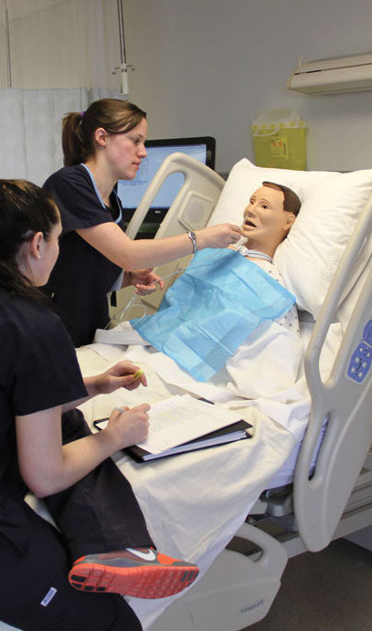 Two nursing students inserting a breathing tube into a nursing simulation dummy