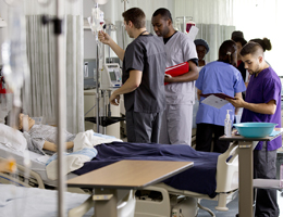 Student nurses by a hospital bed
