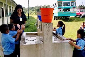 Global Health student helping children wash their hands