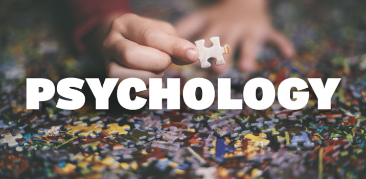 Hands playing with puzzle pieces with the word 'Psychology' written on top of image