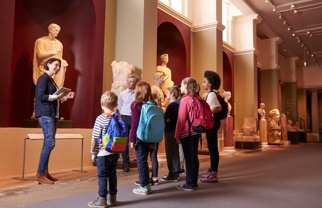museum tour guide explaining ancient statue to kids