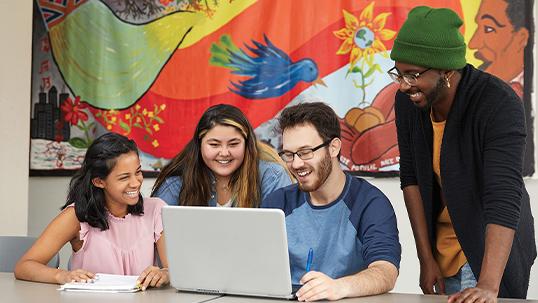 four students around laptop