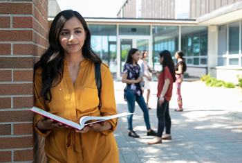 student holding open book with a thoughtful look on her face