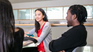 Three students in conversation around desk