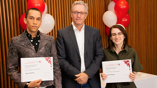 Students pose with professor while holding awards