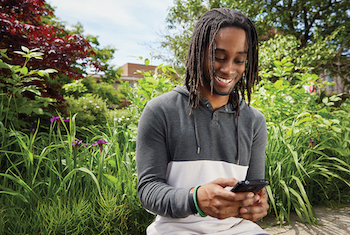 Student smiling while looking at smartphone and sitting outside on York campus