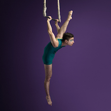 Gymnast holds onto swing in front of purple background
