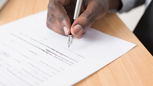A hand hovers over a document holding a pen.
