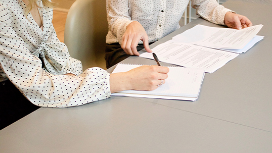 A person sits at a table explaining some forms to another person who is taking notes.