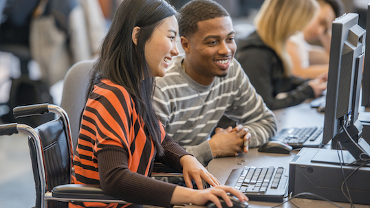 Two students at a computer, watching something and smiling