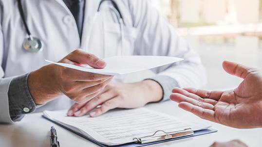 Doctor hands written note to patient