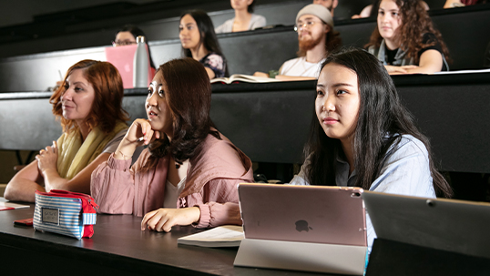 Group of students sit in front row of lecture hall during class