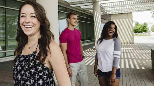 Three York students smiling while standing outside of TEL building on Keele Campus