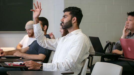 student raising his hand to answer question in seminar