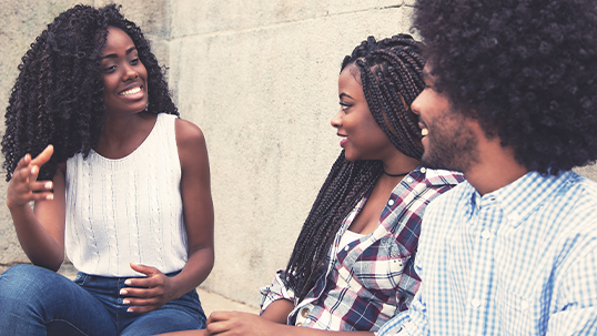 Three black students smiling and talking