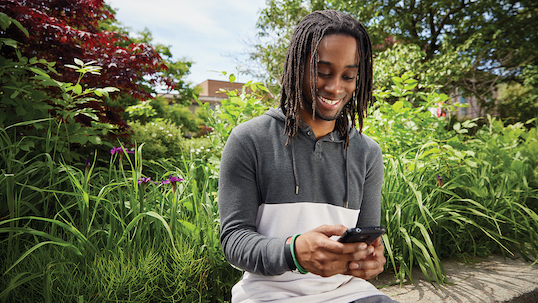Black student smiling and texting