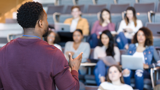 A male college professor gestures while giving a lecture to a group of college students.