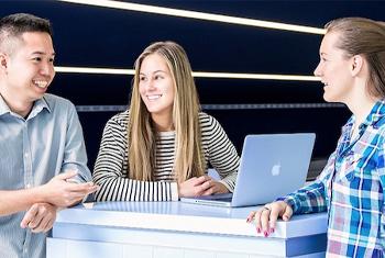 Three students around a desk