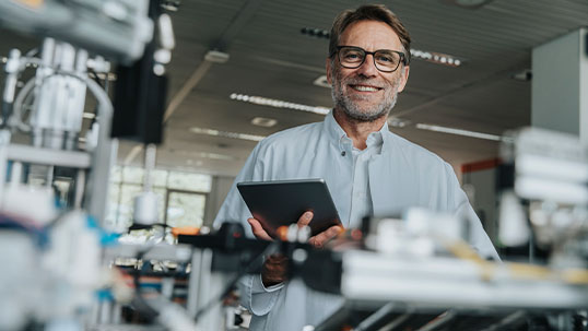 man smiles while holding tablet and standing in science lab
