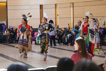 Man and two women wearing Indigenous attire while performing in front of Vari Hall crowd at Keele Campus