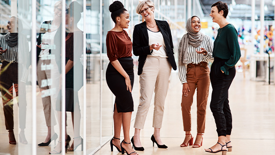 Four women stand talking in a hallway dressed in business attire.