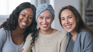 Three racially diverse women are sitting, posing, and smiling at the camera.