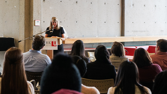 A woman stands in front of a podium that bears the YorkU logo. She speaks to a seated audience.