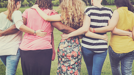 A group of five women walk in a line with their backs turned to the camera and arms around each other.