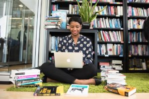 picture of a Black woman sitting on the floor using a laptop with books around her