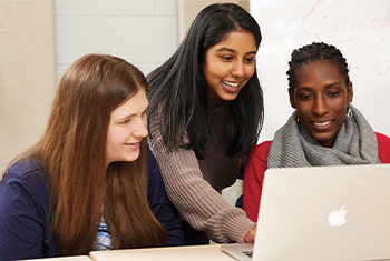 three female students using laptop together