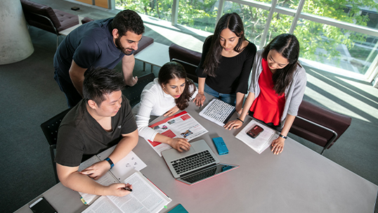 five students using laptop at desk