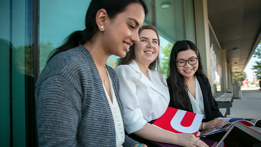 three york students sitting outside on campus in summer