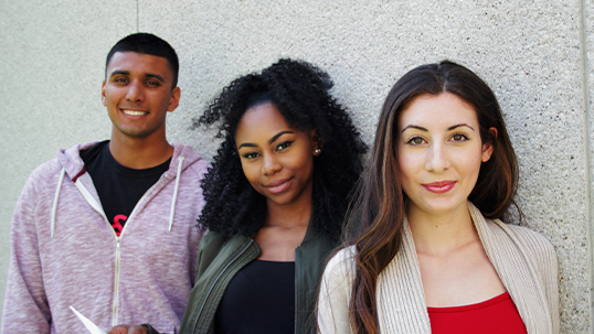 three students smiling for camera