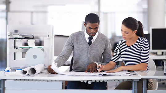 two professionals studying documents on desk