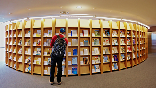 student looking at book shelf in library