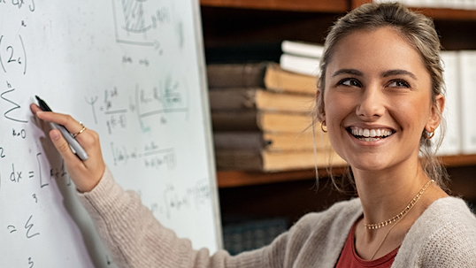 young woman smiles while writing algebraic equation on whiteboard